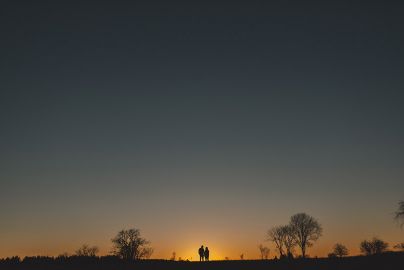 couple holding hands as the sun sets behind them in Ottawa