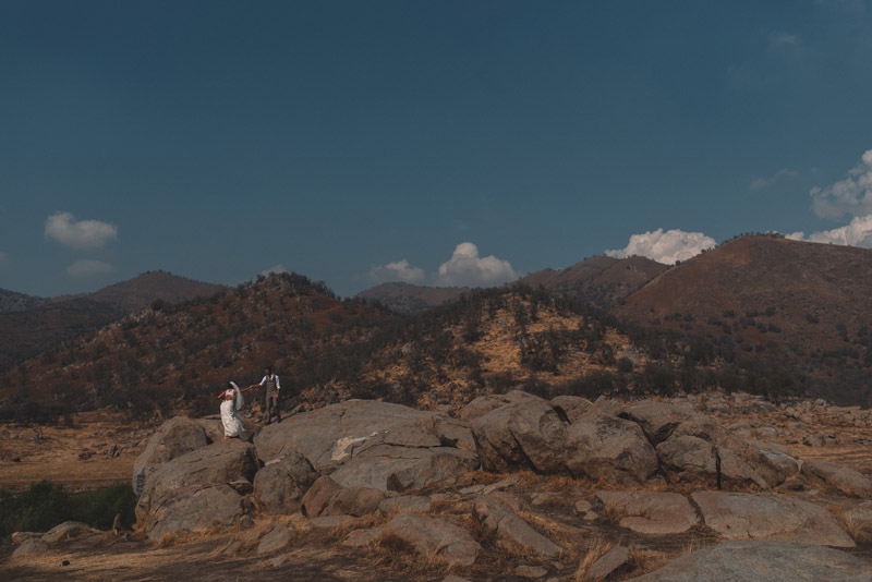 couple climbs up giant rock on their wedding day