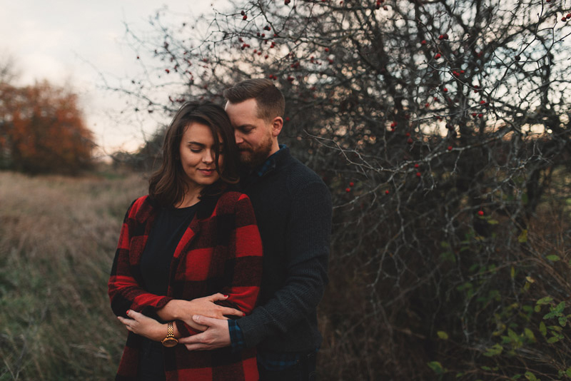 couple hugging in front of a berry tree